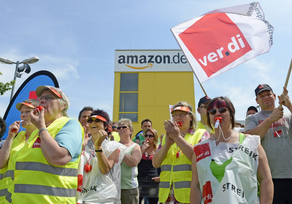 Employees of online retailer Amazon protest during their strike in front of the company's branch in Leipzig, central Germany, Monday, June 17, 2013.  (AP Photo/Jens Meyer)