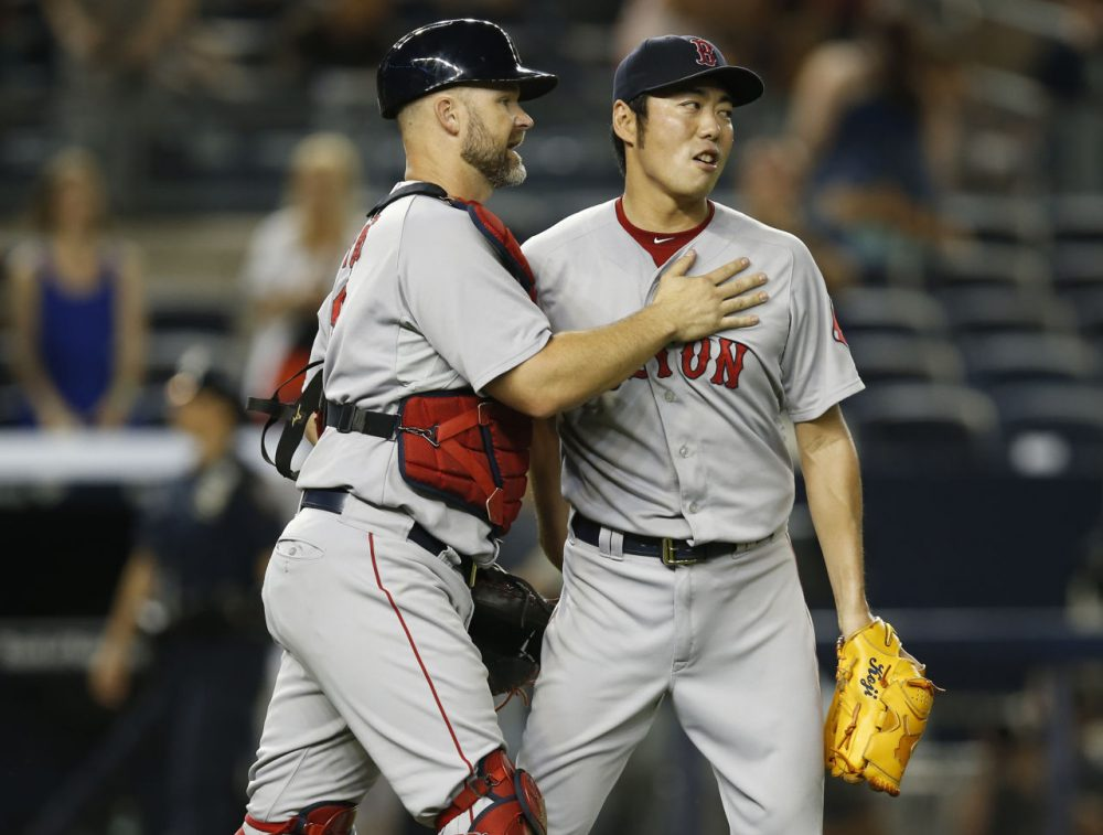 Boston Red Sox catcher David Ross (3) congratulates Boston Red Sox relief pitcher Koji Uehara after defeating the N.Y. Yankees  9-4 Tuesday night. (Kathy Willens/AP)