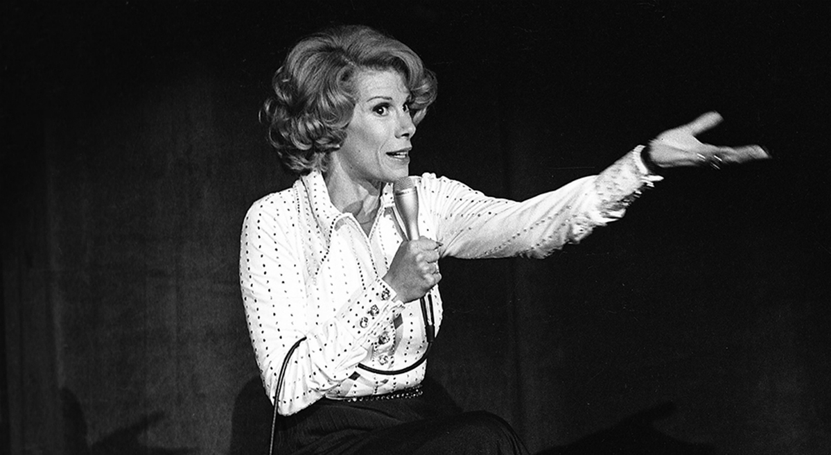 """Renee Graham: """"With Rivers, life, no matter how harsh, cruel or unyielding, was meant to be a punchline."""" Pictured: Joan Rivers performs at the MGM in Las Vegas, Nev., on Aug. 13, 1975. The raucous, acid-tongued comedian died Thursday, Sept. 4, 2014. She was 81. Rivers was hospitalized Aug. 28, after going into cardiac arrest at a doctor's office. (Las Vegas News Bureau/AP)"""