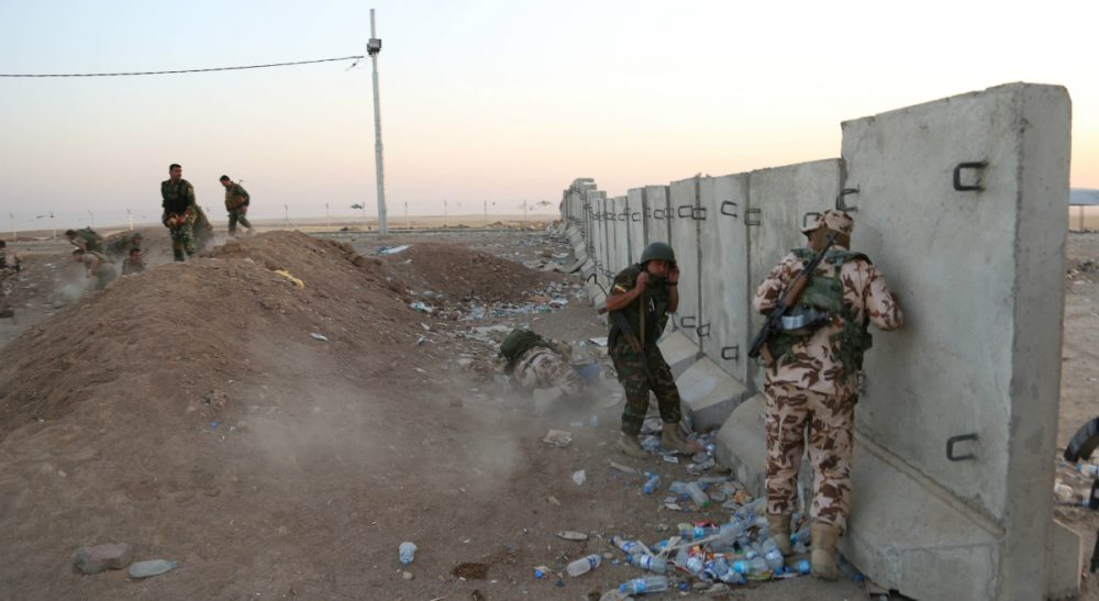 """John Tirman:  """"Rarely has a major military initiative by a president been greeted with such ambivalence. It's not hard to understand why."""" Pictured:  In this Aug. 8, 2014, file photo, Kurdish peshmerga fighters take cover during airstrikes targeting militants of the Islamic State group near the Khazer checkpoint outside of the city of Irbil in northern Iraq. (Khalid Mohammed/AP)"""