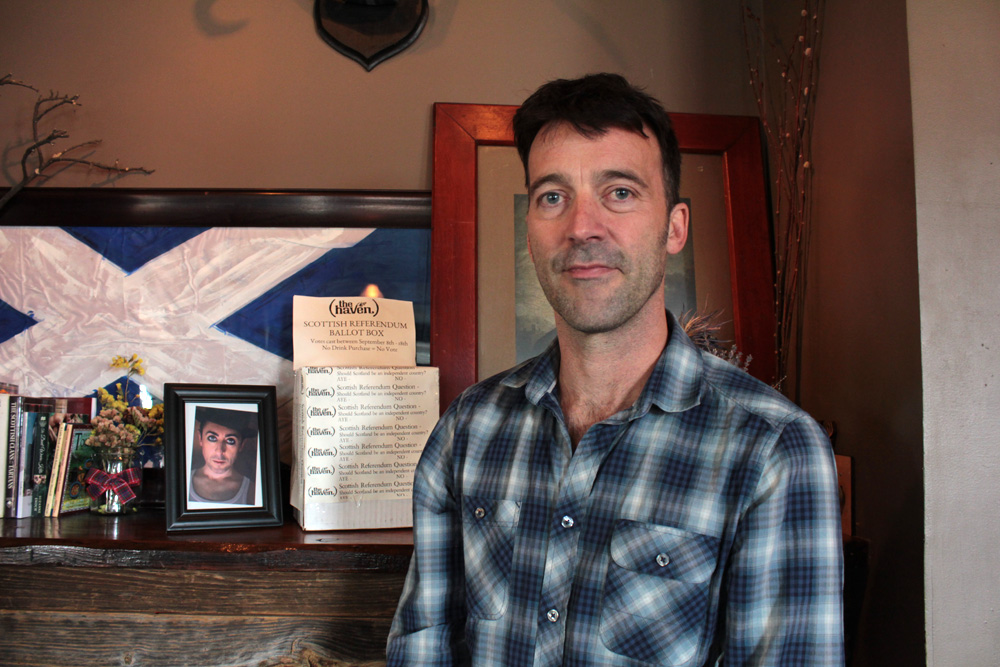 """The owner of the Haven, Scotsman Jason Waddleton, in front of the pub's """"ballot box"""" (Shannon Dooling/WBUR)"""