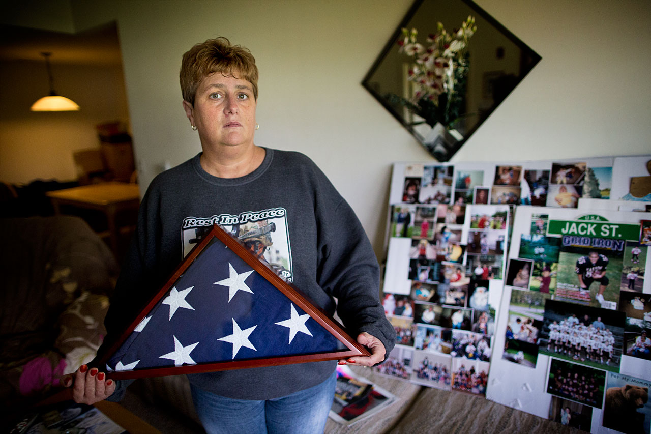 Tammy Sprague Gallagher, whose son, a Massachusetts National Guard soldier, died by suicide last October, stands among tributes to him in her Raynham home. (Jesse Costa/WBUR)
