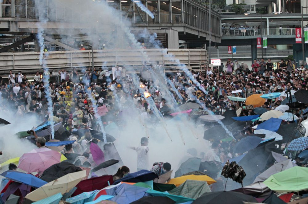 Riot police launch tear gas into the crowd as thousands of protesters surround the government headquarters in Hong Kong Sunday. (Wally Santana/AP)