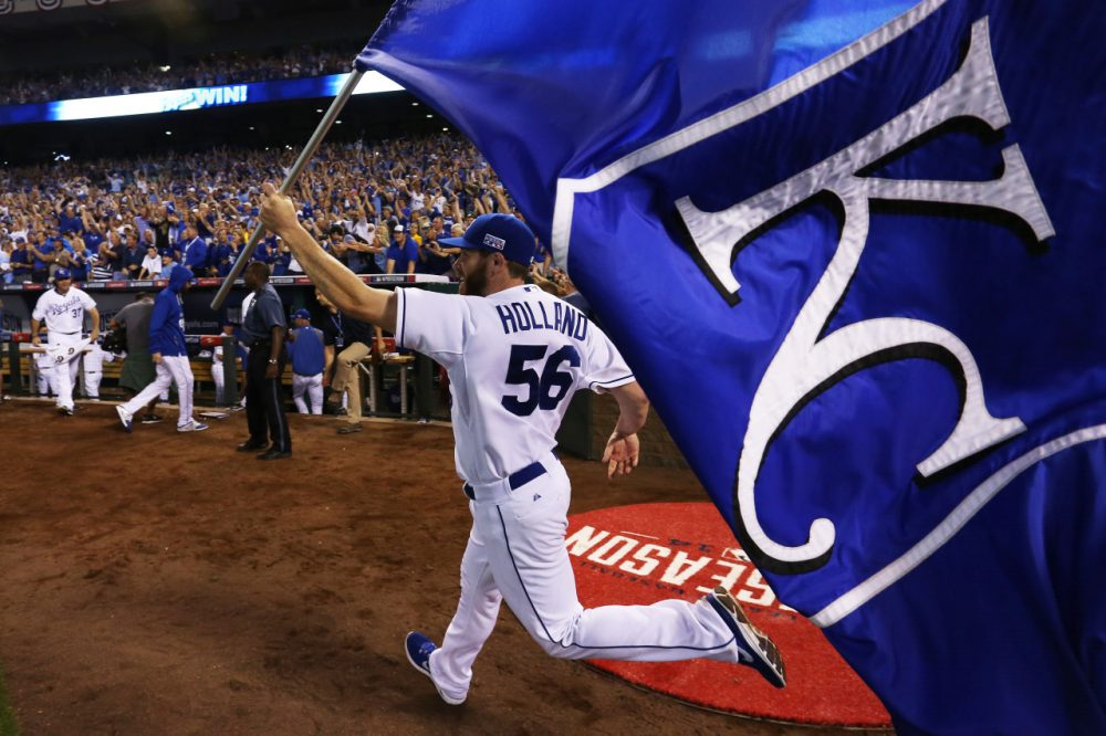 Greg Holland of the Kansas City Royals celebrates with a team flag after they defeated the Oakland Athletics 9 to 8 in the 12th inning of their American League Wild Card game. (Ed Zurga/Getty Images)