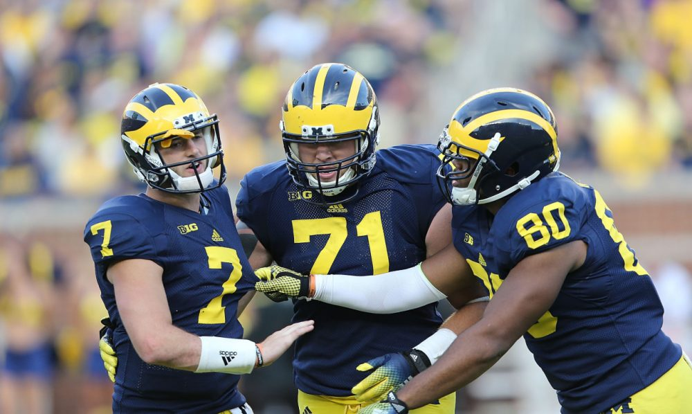 After suffering an illegal hit to the head, Michigan quarterback Shane Morris had to be supported by his teammates. But he remained in the game for two more plays (Leon Halip/Getty Images)