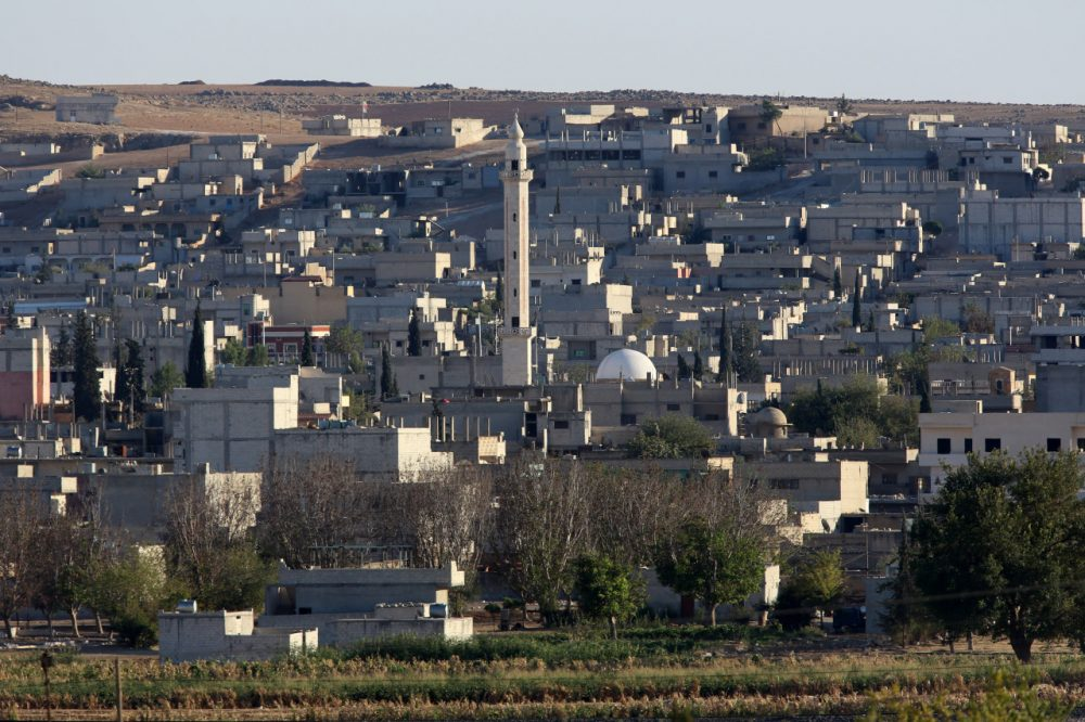 The city center of Syrian Kurdish town of Kobani seen from the Turkish side of border as thousands of new Syrian refugees from Kobani arrive at the Turkey-Syria border near Suruc, Turkey, Wednesday, Oct. 1, 2014. U.S.-led coalition airstrikes targeted Islamic State fighters pressing their offensive against a Kurdish town near the Syrian-Turkish border on Tuesday in an attempt to halt the militants' advance, activists said.(Burhan Ozbilici/AP)