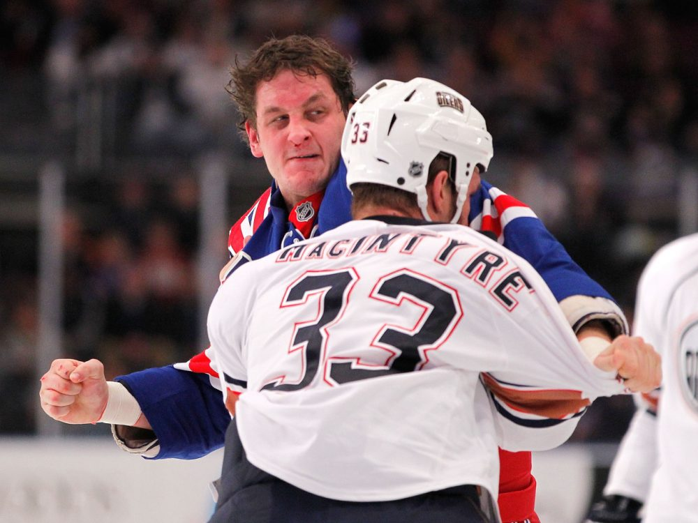 Derek Boogaard (in blue) played the role of hockey enforcer -- and by his own estimate may have suffered hundreds of concussions. (Paul Bereswill/Getty Images)