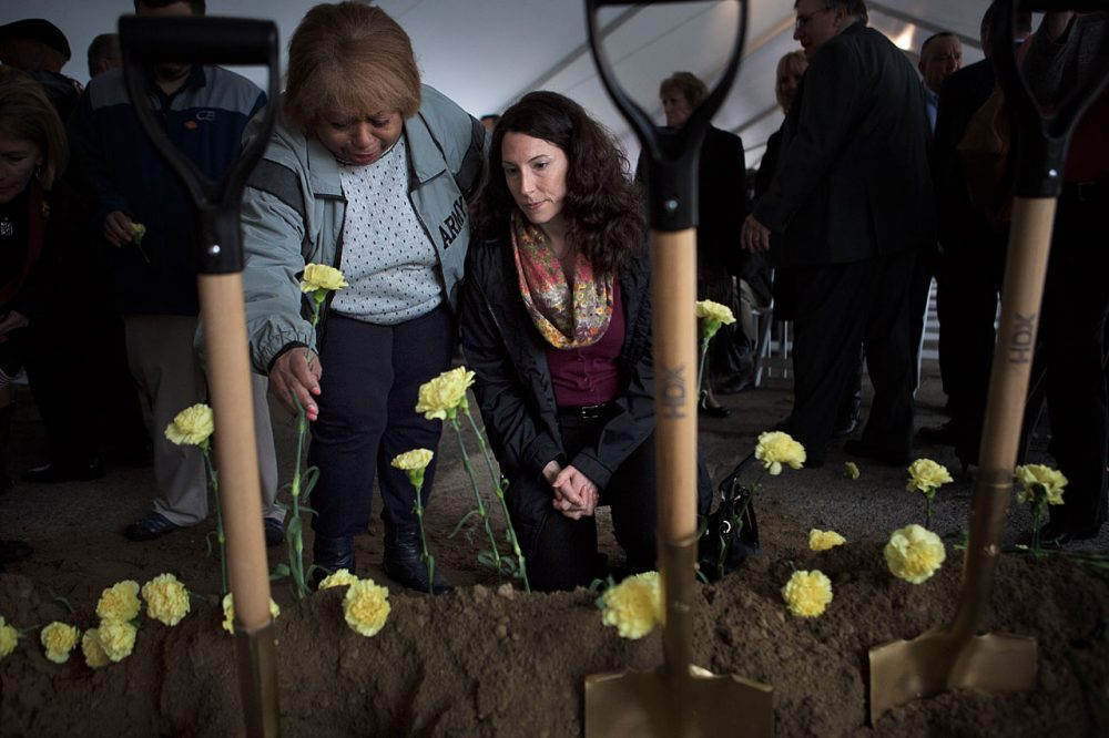 Myrnairis Cepeda, left, sets a yellow carnation into the ground in honor of her daughter who was killed in a car accident in the U.S. after several tours of duty overseas. Maggie Brothers,  right, is an Army Survivor Outreach Services Support Coordinator for Massachusetts whose husband died from exposure to radiation in Qatar. (Jesse Costa/WBUR)