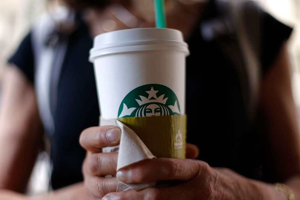 A woman holds a coffee drink outside a Starbucks in Chicago on May 31. (Gene J. Puskar/AP)