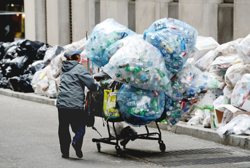A collector of recyclable bottles and cans that can be redeemed for a cash deposit, takes advantage of the recycling that has piled up on William Street in New York. (Henny Ray Abrams/AP)