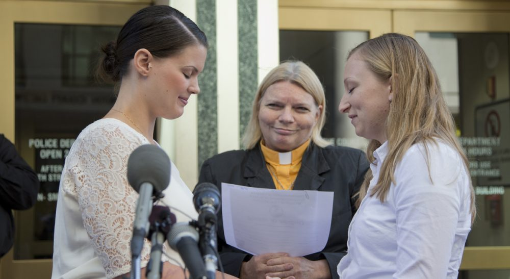 "Holly Jackson: ""Couples demanding rights as spouses and parents are redefining the American family, even in heartland states like Kansas and the Carolinas."" Pictured: Jennifer Melsop and Erika Turner, from Centreville, Va., embrace after they were officially pronounced married. Virginia began issuing marriage licenses to same-sex couples just hours after the Supreme Court's action Monday, October 6, 2014. (Manuel Balce Ceneta/AP)"