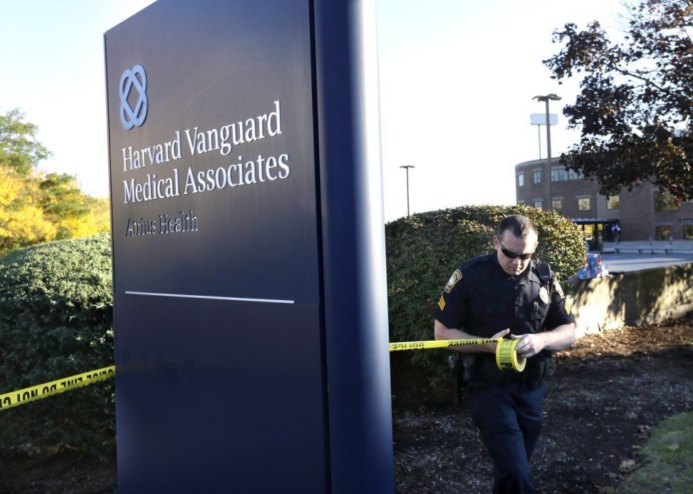 A Braintree, law enforcement official places police tape around a sign to the Harvard Vanguard Medical Associates Sunday, Oct. 12. (Steven Senne/AP)