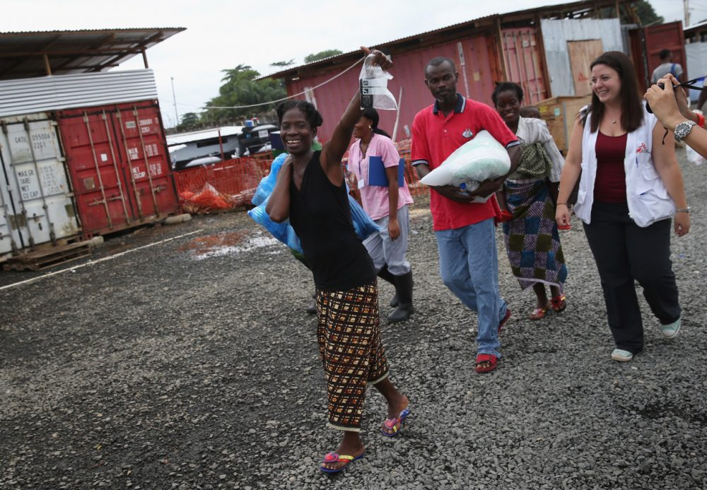 Ebola survivor Sontay Massaley, 37, smiles with Doctors Without Borders (MSF), staff after being released from the MSF treatment center on October 12, 2014 in Paynesville, Liberia. In her hand she held a bag containing her cell phone, which had been disinfected. She said she was there for eight days, after having first arrived sick and tested positive for the disease. (John Moore/Getty Images)