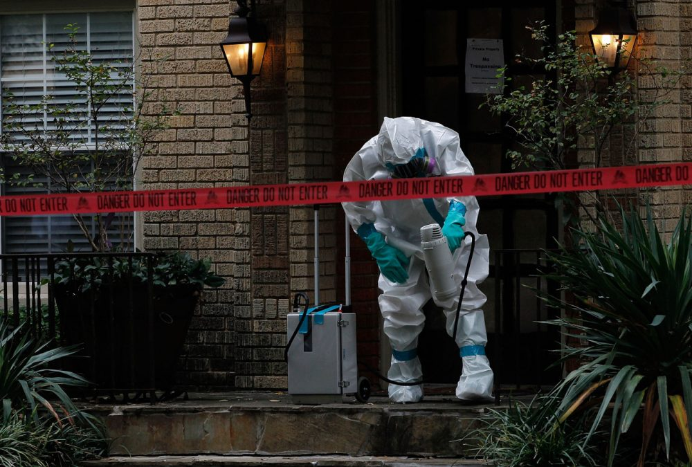 A man dressed in protective hazmat clothing treats the front porch of an apartment where a second person diagnosed with the Ebola virus resides on October 12, 2014 in Dallas, Texas.(Mike Stone/Getty Images)