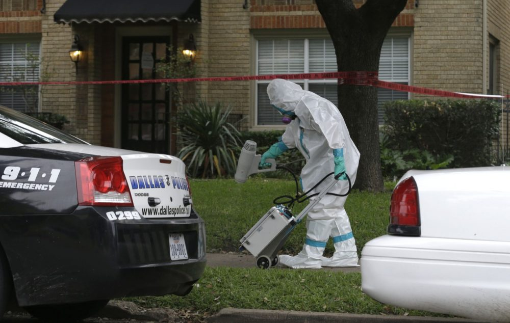 A hazmat worker cleans outside the apartment building of a hospital worker, Sunday, Oct. 12, 2014, in Dallas. (LM Otero/AP)
