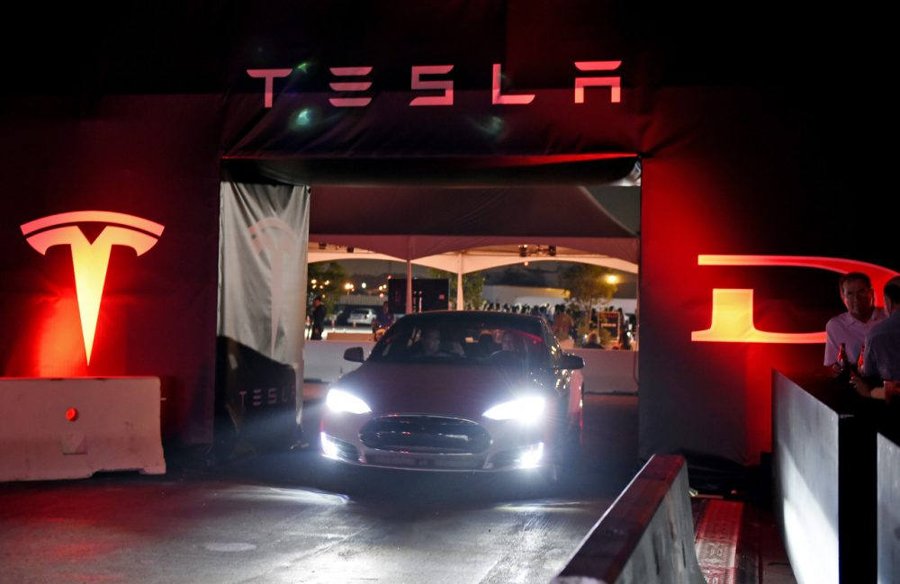 """Tesla owners take a ride in the new Tesla """"D"""" model electric sedan after Elon Musk, CEO of Tesla, unveiled the dual engine chassis of the new Tesla 'D' model at the Hawthorne Airport October 09, 2014 in Hawthorne, California. ( Kevork Djansezian/Getty Images)"""