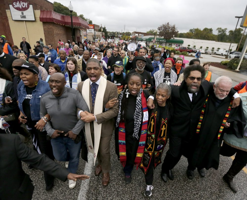 Protesters, including Cornel West, march to the Ferguson, Mo., police station, Monday, Oct. 13. (Charles Rex Arbogast/AP)