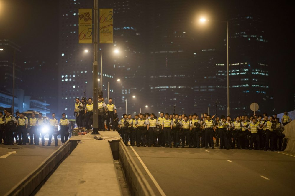 Police prepare to confront pro-democracy protesters outside the central government offices in the Admiralty district of Hong Kong on October 15, 2014. Hong Kong police vowed October 14 to tear down more street barricades manned by pro-democracy protesters, hours after hundreds of officers armed with chainsaws and boltcutters partially cleared two major roads occupied for a fortnight. (Ed Jones/AFP/Getty Images)
