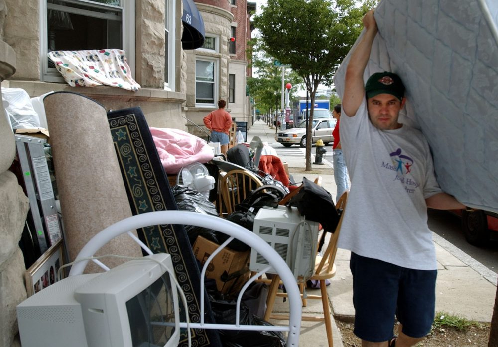 Celso Bias carries out a mattress from his apartment in Allston. (Chitose Suzuki/AP)