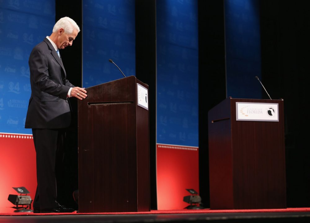 Former Florida Governor and Democratic candidate for Governor Charlie Crist waits next to an empty podium for Republican Florida Governor Rick Scott who delayed his entry onto the stage due to an electric fan that Crist had at his podium as they participate in a televised debate at Broward College on October 15, 2014 in Davie, Florida. (Joe Raedle/Getty Images)