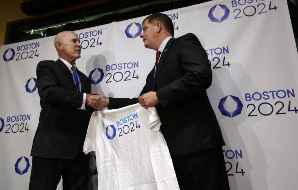 Boston Mayor Marty Walsh, right, is presented with a tee shirt by Ralph Cox, an organizer pursuing an Olympics bid, during an event held to generate public interest in a 2024 Olympics bid for Boston, Monday, Oct. 6, 2014, in Boston. (Steven Senne/AP)