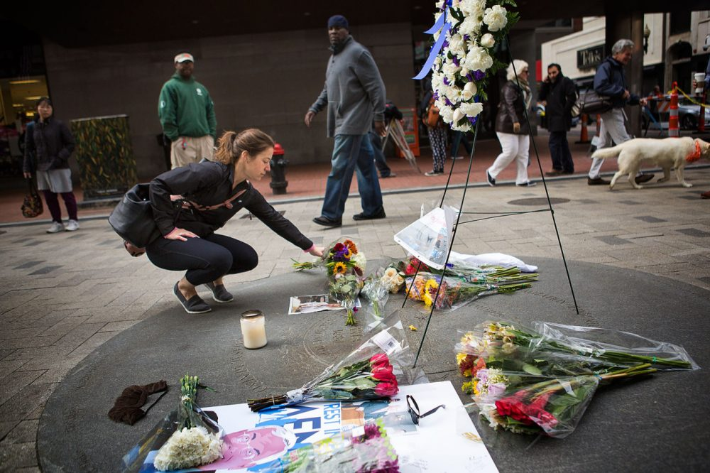 Jessica Sousa, of Somerville, leave flowers to honor the late former mayor of Boston Thomas Menino at a memorial at Downtown Crossing. (Jesse Costa/WBUR)