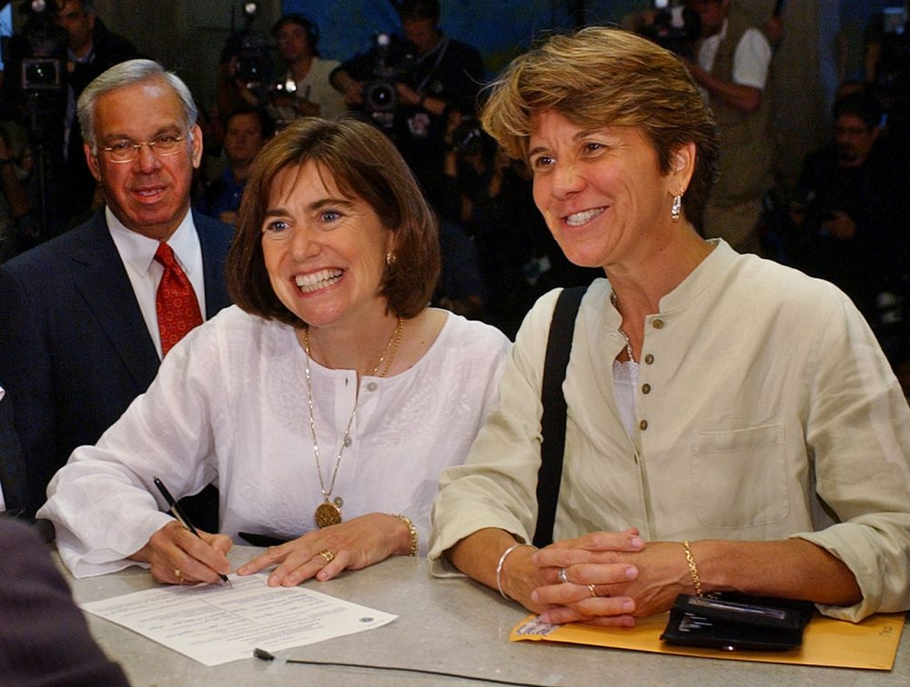 Hillary and her partner, Julie Goodridge, left, the lead plaintiffs in the Massachusetts gay marriage lawsuit, fill out their marriage license application — the first in the nation for same-sex couples — with Menino looking over their shoulder, at Boston City Hall in Boston in May 2004. (Charles Krupa/AP)