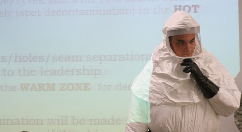 Cpl. Zachary Wicker shows the use of a germ-protective gear in Fort Bliss, Texas, Tuesday, Oct. 14,  2014. About 500 Fort Bliss soldiers are preparing for deployment to West Africa where they will provide support in a military effort to contain the Ebola outbreak. /Juan Carlos Llorca/AP)