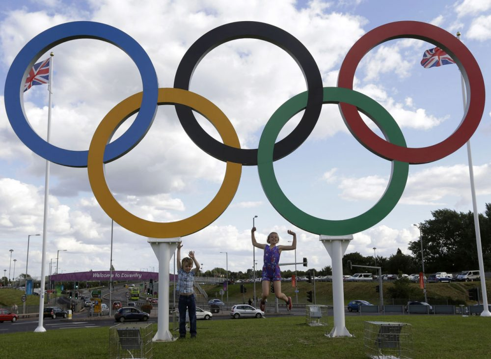 In this July 28, 2012 file photo, children posed for photos under the Olympics rings in Coventry, England. Boston, Los Angeles, San Francisco and Washington are in the running for a possible U.S. bid to host the 2024 Summer Olympics. (Hussein Malla/AP)