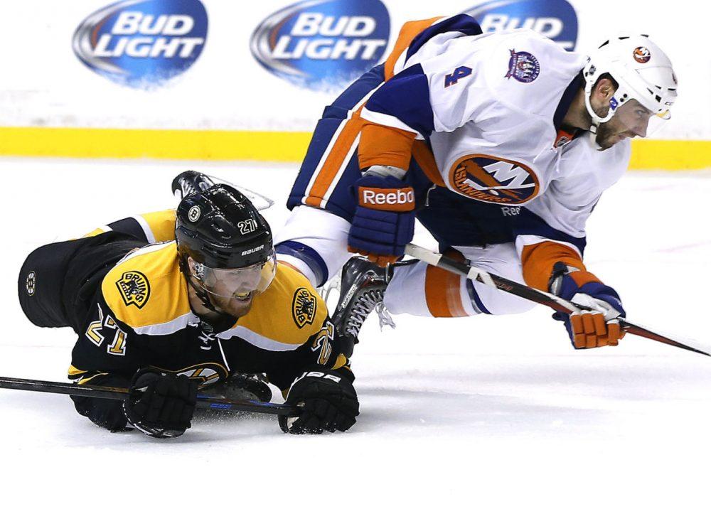 Boston Bruins defenseman Dougie Hamilton (27) slides on the ice after colliding with New York Islanders defenseman T.J. Brennan (4) during the second period of a preseason hockey game in Boston. The Islanders won 5-3. (Elise Amendola/AP)