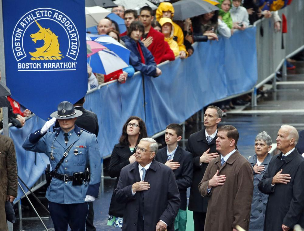 Former Boston Mayor Thomas Menino, center, Boston Mayor Marty Walsh, third from right, and Vice President Joe Biden, right, salute along with the family of Boston Marathon bombing victim Martin Richard, behind, during a remembrance ceremony at the finish line on Boylston Street in Boston, on April 15, 2014. (Elise Amendola/AP)