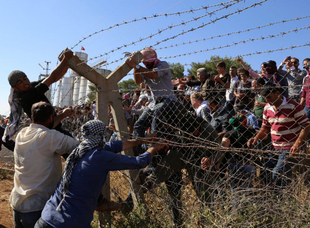 """In this Friday, Sept. 26, 2014 photo, Kurds from Turkey, right, and Syria break down the barbed wire at the Turkey-Syria border near Suruc, Turkey. Turkish President Recep Tayyip Erdogan said Friday that a """"no-fly zone"""" should be created in Syria to protect part of it from attacks by Syria's air force. In his comments to reporters on his return from the U.N. General Assembly in New York, Erdogan did not specify where such a zone should be located. (AP)"""