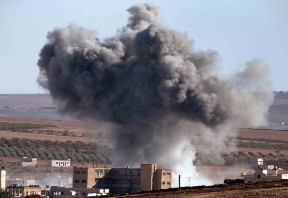 Thick smoke from an airstrike by the US-led coalition rises in Kobani, Syria, as seen from a hilltop on the outskirts of Suruc, at the Turkey-Syria border, Monday, Oct. 20, 2014 Kobani, also known as Ayn Arab, and its surrounding areas, has been under assault by extremists of the Islamic State group since mid-September and is being defended by Kurdish fighters. (AP Photo/Lefteris Pitarakis)