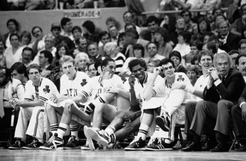 Four strangers to the Celtics bench react as they get to sit out the fourth quarter of a playoff rout while the rest of the team carries on to a Boston victory over the Atlanta Hawks, 132-99, Tuesday, May 6, 1986 in Boston. (AP)