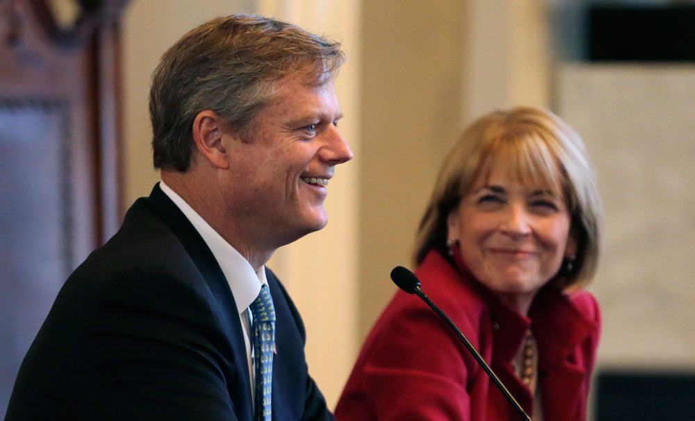Republican nominee for governor Charlie Baker smiles as he addresses a forum in Boston on Sept. 24. At right is Democratic nominee Martha Coakley. (Charles Krupa/AP)