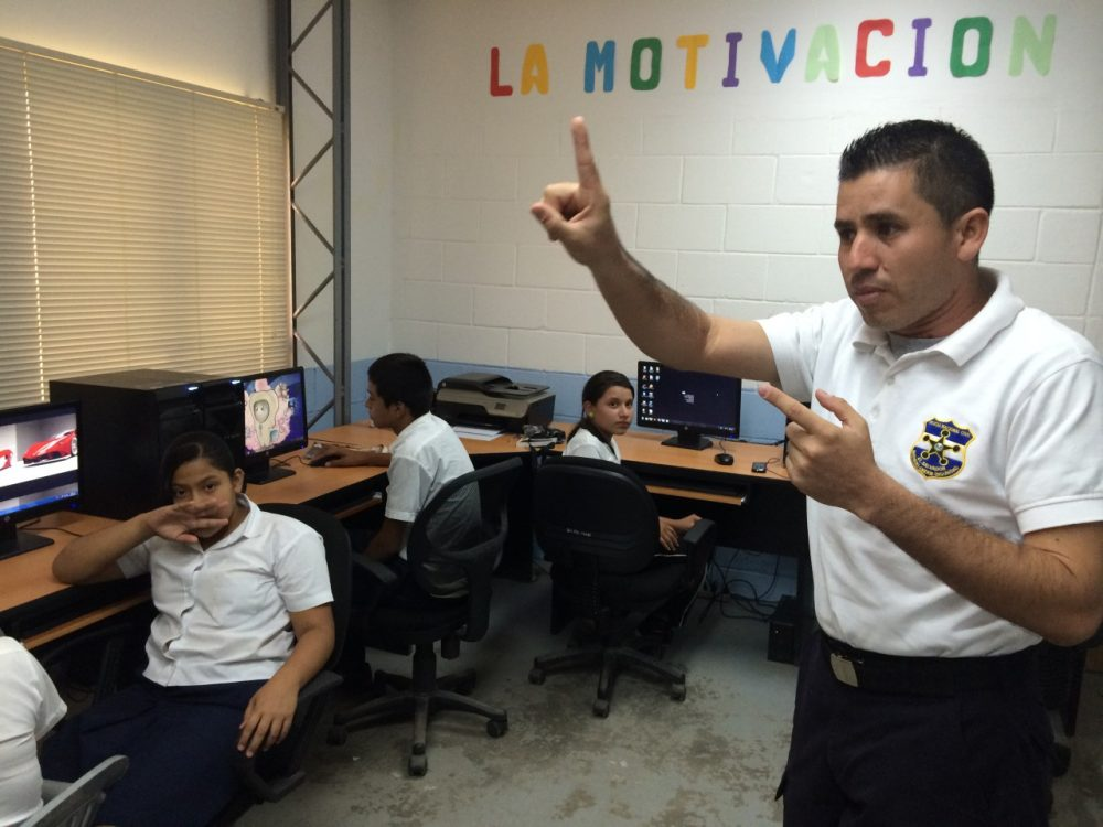 A police officer in Santa Ana, El Salvador teaches a group of sixth graders how to use computers as part of the GREAT program. (Jude Joffe-Block/KJZZ)
