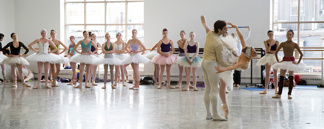 "Ashley Ellis and Eris Nezha rehearse their pas de deux as corps de ballet dancers wait for their entrance during a costume run-through of ""Swan Lake"" at the Boston Ballet studios. (Lawrence Elizabeth Knox)."