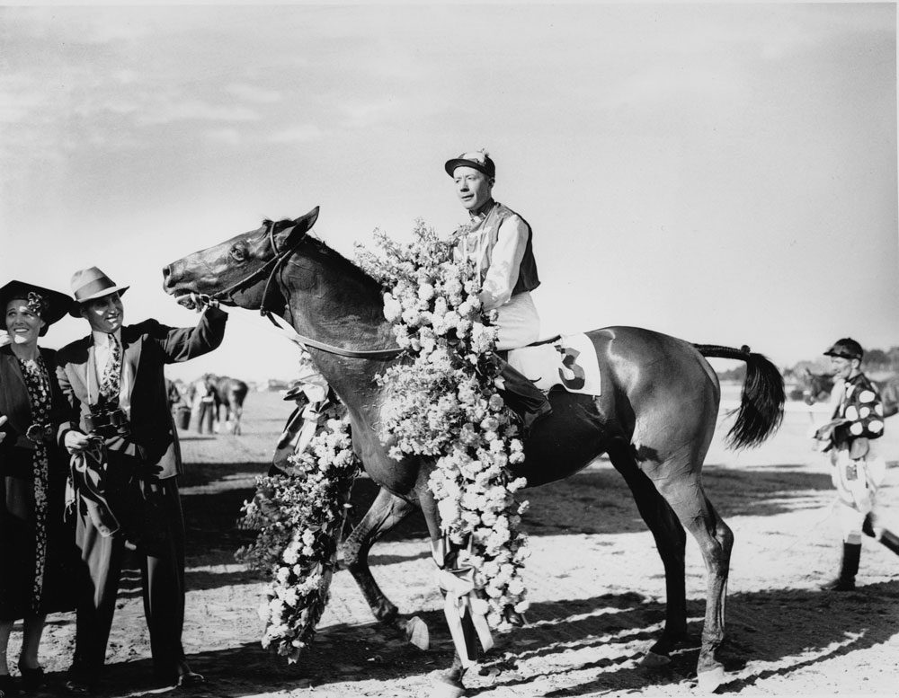 "Seabiscuit is shown with jockey Johnny ""Red"" Pollard after winning the Massachusetts Handicap at Suffolk Downs on Aug. 7, 1937. (AP)"