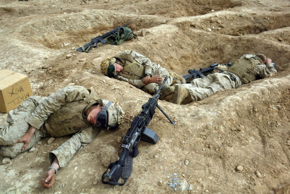Cpl. Will McDermott, front, from Phoenix, Ariz and other Marines from the 1st Battalion 5th Marines sleep in their fighting holes in Fallujah, Iraq in 2004. (John Moore/AP)