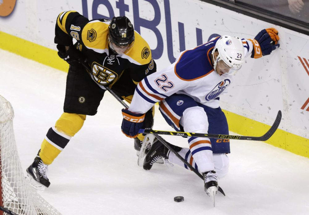 Boston Bruins right wing Reilly Smith (18) and Edmonton Oilers defenseman Keith Aulie (22) vie for the puck during the third period of an NHL hockey game Thursday. (Charles Krupa/AP)