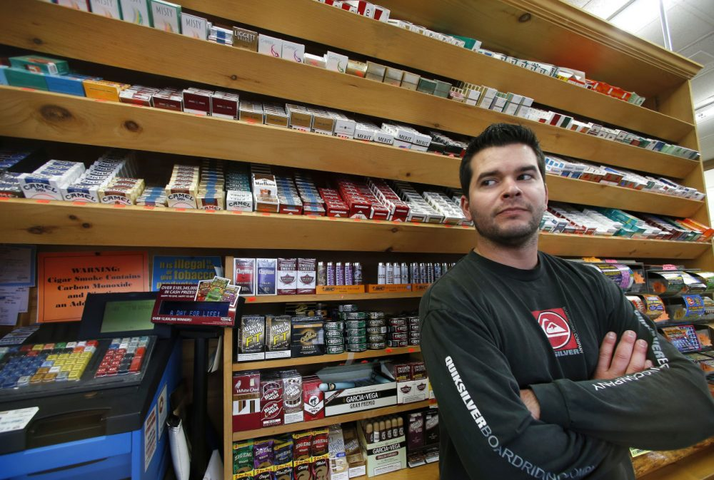 Brian Vincent poses in front of a large display of tobacco products at Vincent's Country Store in Westminster on Nov. 6. Local officials are contemplating what could be a first: a blanket ban on all forms of tobacco and e-cigarettes, leaving some shop owners fuming. (Elise Amendola/AP)