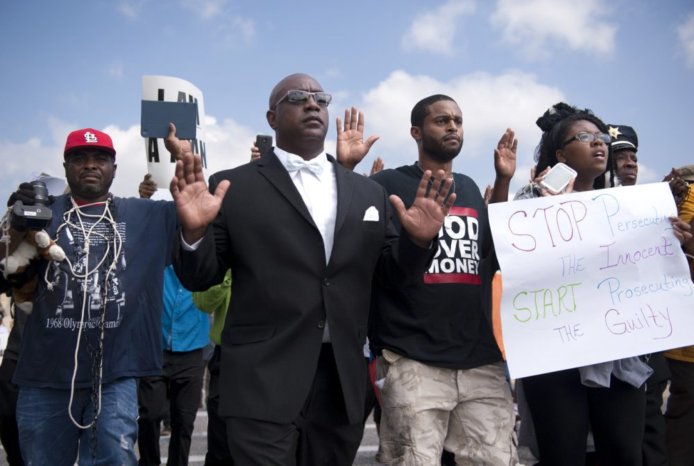 Protestors march along Florissant Road in downtown Ferguson, Mo. Monday, Aug. 11, 2014. The group marched along the closed street, rallying in front of the town's police headquarters to protest the shooting of 18-year-old Michael Brown by Ferguson police officers on Saturday night. (Sid Hastings/AP)
