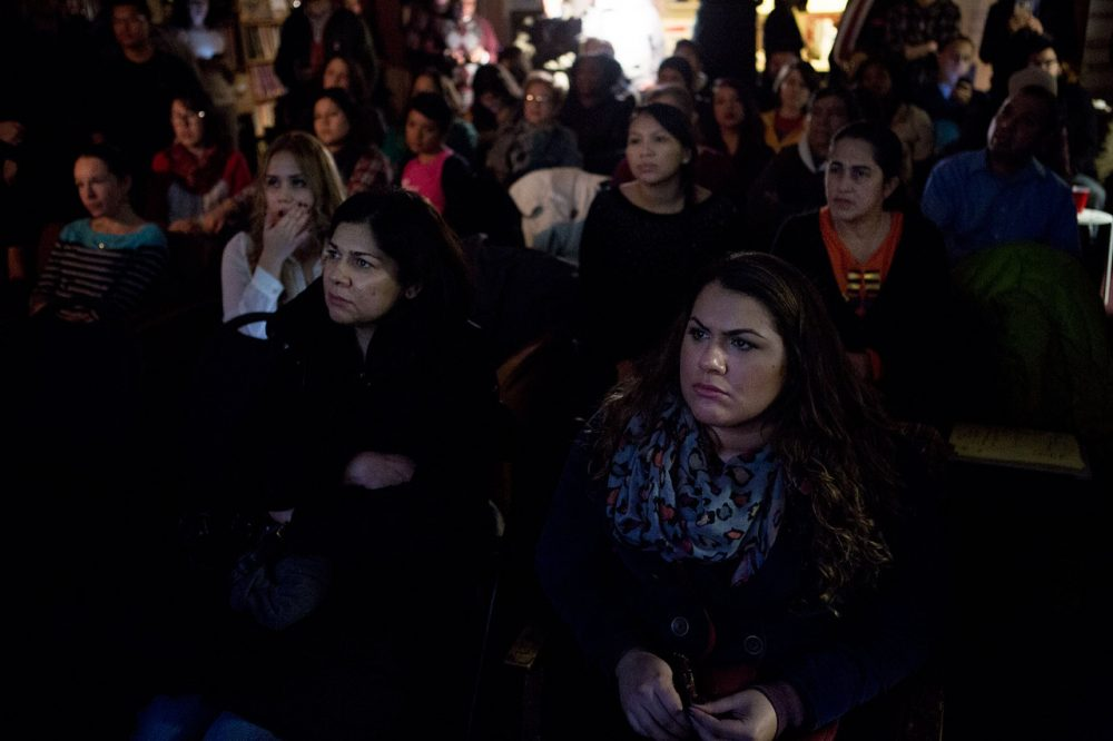 With a subdued but hopeful group, Leila Santana and her daughter Lara of Medford (in front) watch President Obama's televised address to the nation announcing his executive action on immigration at the Student Immigrant Movement offices in Boston. (Jesse Costa/WBUR)
