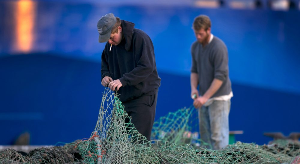 David Ropeik on overfishing and its devastating effects off- and on-shore. Pictured: Fishermen Ed Stewart, left, and Tannis Goodsen mend groundfishing nets on Merrill Wharf in Portland, Maine in 2013. (Robert F. Bukaty/AP)