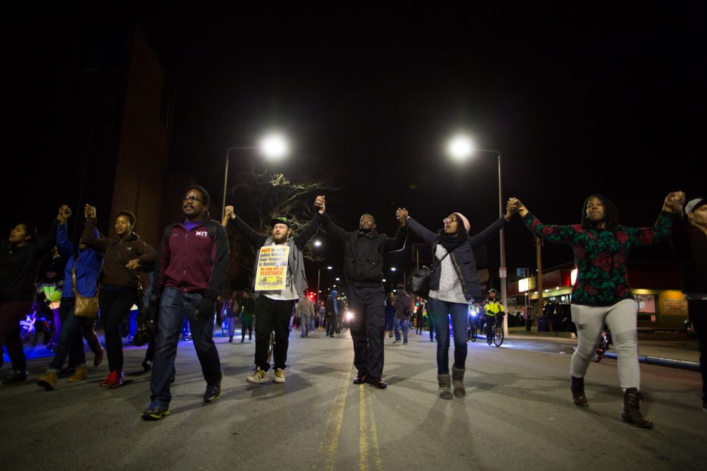 In Boston, hundreds of protesters marched through the city streets in solidarity with demonstrators in Ferguson in the aftermath of a grand jury's decision to not indict a white officer who shot and killed an unarmed black teen.