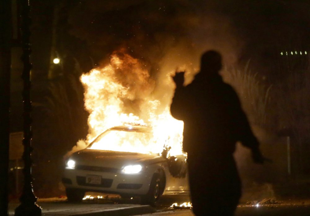 A police car is set on fire after a group of protesters vandalize the vehicle. (Charlie Riedel/AP)