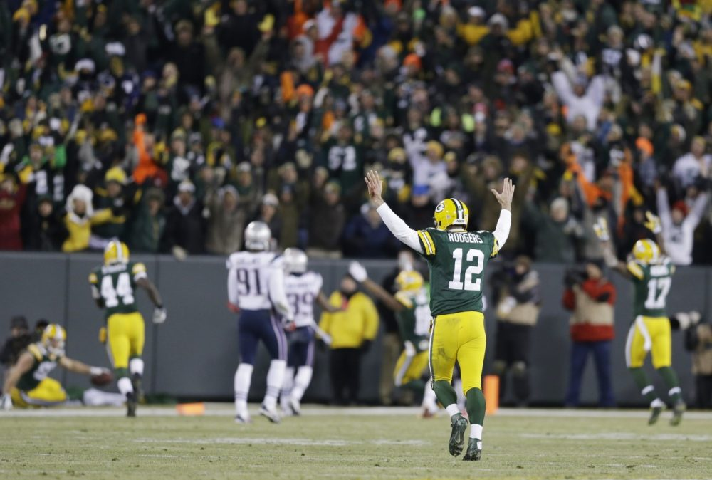 Green Bay Packers quarterback Aaron Rodgers (12) celebrates a 45-yard touchdown pass to Jordy Nelson during the waning moments of the first half against the New England Patriots Sunday in Green Bay, Wis. (Tom Lynn/AP)