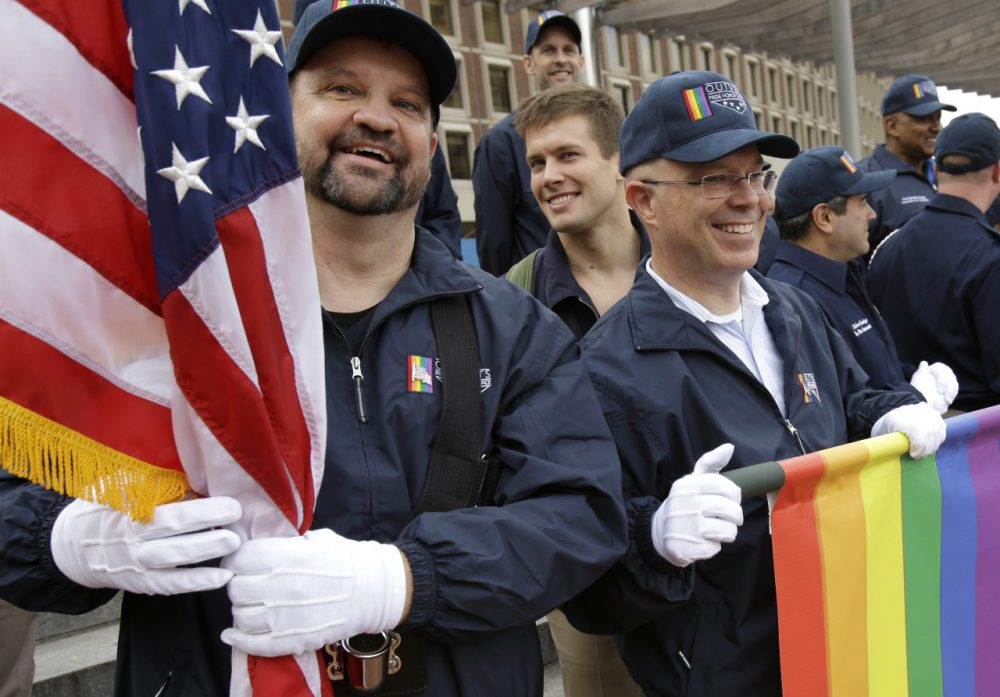 Retired U.S. Air Force Master Sgt. Eric Bullen, of Westborough, Mass., left, holds an American flag as U.S. Army veteran Ian Ryan, of Dennis, Mass., front right, rolls up an OutVets banner after marching with a group representing LGBT military veterans in a Veterans Day parade for the first time in Boston on Tuesday, Nov. 11, 2014. (Steven Senne/AP)