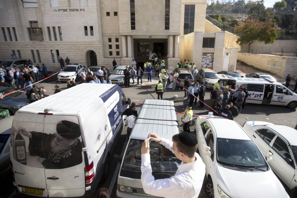 An ultra-Orthodox Jewish youth takes a picture at the scene of a shooting attack in a synagogue in Jerusalem Tuesday. (Sebastian Scheiner/AP)