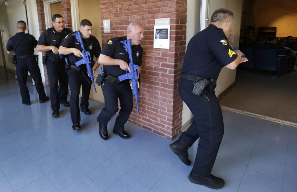 Officers from the Methuen, Mass., police department carry training weapons as they search the halls of a school during a demonstration to test a new system to track gunman in schools on Nov. 11, 2014. (Charles Krupa/AP)